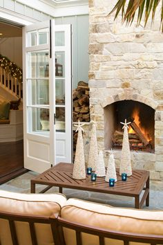 A few cone-shaped seashell statues and votives add cheer to this outdoor living room - Traditional Home®
