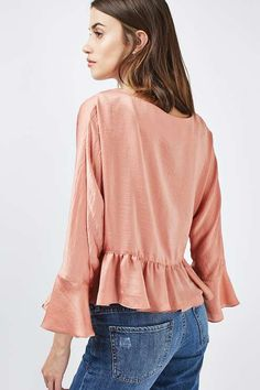 Embrace an elegant flourish with the ruffle wrap front blouse. Featuring a feminine flounce at the hem and sleeves, this dusty pink hammered satin-feel style is perfect with a black ripped jean for an edgy contrast. #Topshop