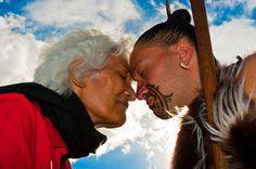 A Maori man with ta moko (facial tattoo) and an elderly Maori woman doing hongi (traditional Maori greeting) , Te Puia (New Zealand Maori Arts & Crafts Institute), Rotorua, New Zealand