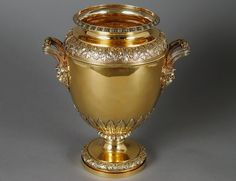 """by Paul Storr English. London. 1820. Of urn form with detachable collar chased with leaves on a stippled ground with reeded handles terminating in bearded male masks, raised on a circular pedestal base. Height 11"""""""