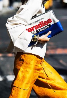 A graphic clutch is paired with a loose white top and suede trousers