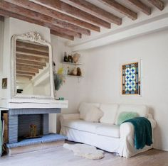 A Gallery of Cozy Cottage Interiors - beamed ceiling and fuzzy throws add warmth. From Rue.