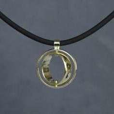 twee gouden trouwringen waarvan de binnenste ring cardanisch is opgehangen in de buitenste ring