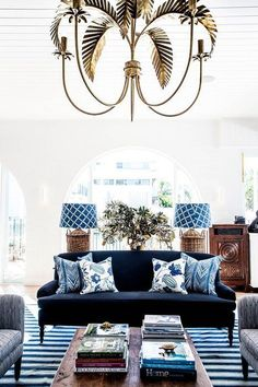 Blue prints and a palm leaf chandelier make this blue and white living room cool and chill all at once.