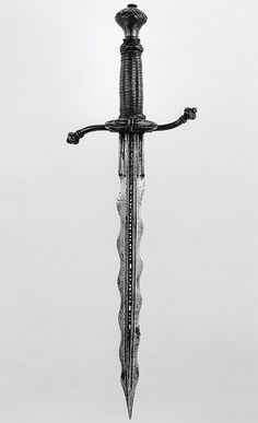 "Parrying Dagger (pugnale bolognese) Dated: 1550–75 Culture: Italian Medium: partly gilt steel, brass, and wood Measurements: wt. 15 oz. (425 g) Designed to be used together with a rapier, this dagger is fitted with a side ring, recurved quillons, and a depression at the base of one side of the blade to accommodate the thumb and facilitate a firmer grip. The waves in the blade may be intended to act like ""speed bumps"" in breaking the impact of a blow from an opponent's blad"