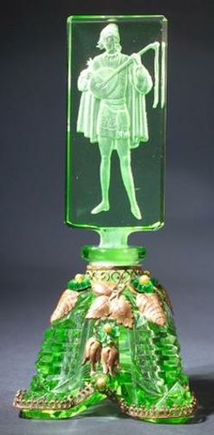 A Czechoslovakian perfume bottle, circa 1920s, in green crystal, with jeweled metalwork.