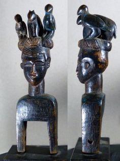 Art d'Afrique - Auction GRANDE POULIE DE METIER A TISSER GOURO (Côte d'Ivoire). Anthropomorphe en bois sculpté, le visage coiffé de trois animaux (deux oiseaux et un mammifère). Trace de peinture bleue. 22,5 x 6,5 cm.