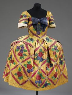 Costume for Mariuccia in Massine's ballet Les Femmes de bonne humeur designed by Leon Bakst, Diaghilev Ballet 1917. Short-sleeved, panniered dress in gold satin with blue bow on the bodice, appliqued with a pink 'lattice' each enclosing a spray of stylized flowers and leaves in pink, green, magenta and blue.