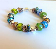 "Sterling Silver European Style Bracelet by ClearWaterDesignsbyK, $26.67 http:clearwaterdesignsbyk.etsy.com http://clearwaterdesigns.info This Pretty European Style Bracelet features Blue, Green & Yellow Large Hole Lampwork Beads & Heart Shaped Silver Tone Spacer Beads with ""Love"" written on them. The bracelet is 925 Sterling Silver Snake Chain with an easy snap on clasp."