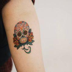 Pequeño tatuaje de una calavera de azúcar situado en el...