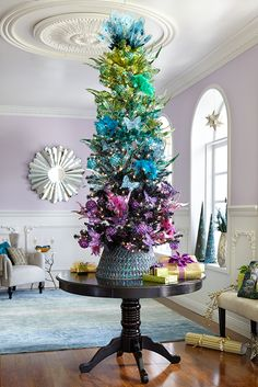 """Peacocks never miss an opportunity to show off and neither should you. Trim Pier 1's colorful Flights of Fancy Christmas Tree with decorative plumage, jewel tones, and our new gilded tree collar. This holiday is truly worthy of the word """"fancy"""" like the brilliant birds that inspire it."""