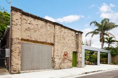 Architect Richard Smith designed the conversion of an old brick building in Sydney, Australia, that was once an auto repair shop, into a home with cathedral ceilings and exposed timber beams