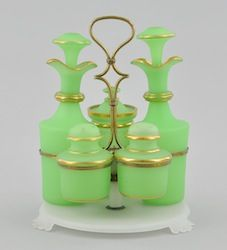 A Victorian Bristol Green Glass Condiment Set ~ Frosted apple green glass with gilt highlights ~ Two cruets with stoppers ~ Jam pot ~ Salt and pepper shaker ~ Seated on frosted white glass footed platform with brass holders and handle on frosted glass stem with brass collar