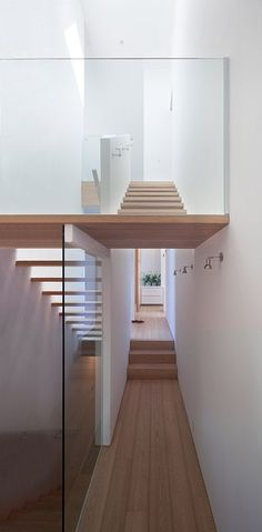 Vancouver house by Canadian studio Splyce Design features a lopsided roof that follows the line of the staircase. Stairs between the three floors are at the north-facing front of the house, which is the darkest part of the building. Open stair treads, glass balustrades and a rooflight at the top of the stairwell have been added to increase the flow of natural light here.