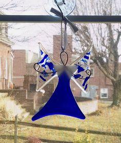 Cet Ange en verre fusionné «céleste» peut être utilisé comme un ornement ou un capteur de fenêtre. Il mesure 3 x 4 et est suspendu à un ruban bleu noeud papillon. Un cintre ventouse est inclus.  La jupe est faite avec du verre cathédrale bleu cobalt. Les ailes sont faites avec du verre clair cathédrale avec un verre de confettis bleu fondu sur le dessus. Le corps du centre est fait avec du verre opalescent blanc. Fil est fondu dans le verre pour former la tête et les bras.  Les bras…