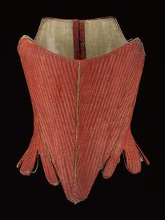 Woman's stays of linen and stiffening, the exterior of red linen and interior of cream linen. Lengths of cane have been sewn into the interior with rows of vertical stitches. The reverse of the stays can be adjusted with a length of linen interlaced through eyelets at the centre back opening. The lower edge of the stays is deeply dentated: English, c. 1730 - 50.  Museum reference A.1905.983