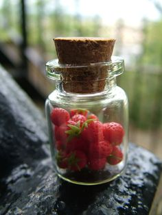 glass bottle filled with mini strawberries