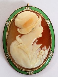 "14KT GOLD, CARVED CAMEO & ENAMEL PENDANT/BROOCH, L 1 1/2"":An oval shell carved in cameo with the bust length profile of a vintage lady, set within a 14kt yellow gold mount trimmed with green and white enamel. The clasp stamped ""14K""."