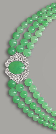 JADEITE AND DIAMOND NECKLACE Set to the front with a translucent jadeite cabochon of apple green colour, to an openwork surround set with circular-cut diamonds, completed by a triple-strand graduated jadeite bead necklace, to a clasp set with jadeite cabochons and circular-cut diamonds.
