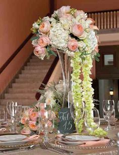 Arrangement with elegant flowers, such as garden roses, hydrangea, orchids then accents of sage.