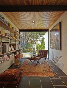 String shelving lines one wall of the library. On the facing wall is 'Conversation of Momentum' by Annika Koops. A 'Barcelona' chair by Ludwig Mies van der Rohe and Lilly Reich, and a 'Diamond' chair by Harry Bertoia for Knoll sit on an antique Kashmir rug. Outside is a sculpture by John Edgar.