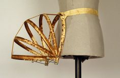 """Bustle Date Made: 1884-1888  Description: Bustle; """"Hazel Bustle"""", patented applied for. Narrow collapsible bustle. Bustle structure constructed of cotton cloth-covered metal-edged stays attached with grommets. Cotton tape waistband with metal buckle."""