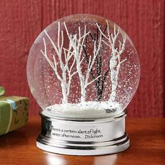 """SOLITUDE SNOWGLOBE -- Emily Dickinson imbues a wintry woodland scene with poetic significance: """"There's a certain slant of light, winter afternoon."""" Boxed for gift giving. 4""""dia. x 4-3/4""""H."""