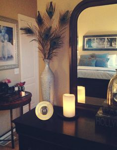 Peacock feathers from the Cheyenne Mountain Zoo look so glam! Soothing neutral bedroom with pops of turquoise.