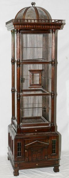 """MAITLAND SMITH, MAHOGANY BIRDCAGE, H 84"""", W 24"""", L 24"""":fluted column corners, gallery with a bent glass dome at the top; narrow pull out waste tray below cage. Classical design on cabinet door at the bottom with miniature framed windows. Narrow storage drawer at very bottom with brass pull all supported on square feet."""