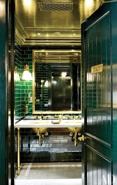 In the bathroom of Ralph Lauren's Manhattan Polo Bar, emerald-green tile and brass details lend retro glamour to a washroom.