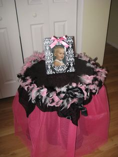 My first attempt @ a Tutu Table.  This is for my daughter's baby shower.  The color scheme is black, pink, and white.  We have baby pictures scattered through-out of her and her fiancee as an added fun touch.  The best part is she can keep the table and use it in the baby's room!