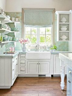 White kitchen with green and aqua backsplash.