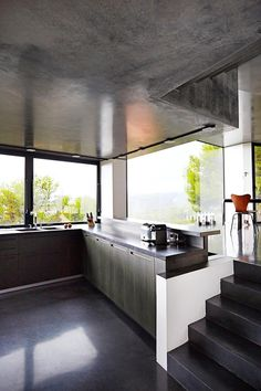 Concrete features throughout the house, serving to link the rooms. The raised ledge along the kitchen bench can be used as seating – perfect to sit and chat to whoever may be in the kitchen or to simply enjoy the view. Kitchen Benches, Black Kitchens, Concrete, Kitchen Design, Home And Family, Lisa, Stairs, Rooms, Urban