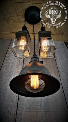 You are looking at an original triple upcycled whiskey bottle pendant light and a custom lamp shade pendant, two bottle lights custom painted and staggered perfectly for a very unique looking centerpiece! I took two upcycled whiskey bottles cut them and polished them and fit perfectly on a custom flat black ceiling canopy, arranged with a vintage two wire twisted cloth covered cord in rayon black, and fitted with three different styles of Edison bulbs for a very distinctive look!