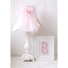 This ornate kids table lamp has been painted pink and adorned with a bell-shaped scalloped shade, made with the finest pink Dupioni Silk and finished with a large tulle bow, satin ribbons, and a dream
