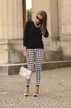Black top, white statement necklace, houndstooth patterned jeans and black shoes, white purse