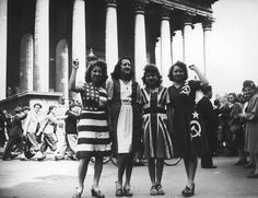 A group of women wearing dresses representing flags of the Allied powers outside the Eglise de la Madeleine on VE Day in Paris, 8th May 1945. ""