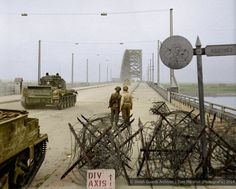 Two soldiers watch as 'Cromwell' tanks of the Guards Armoured Division of the 2nd Armoured Recon Battalion the Welsh Guards cross Nijmegen bridge in the Netherlands, Thursday, the 21st of September 1944. This bridge was located approximately ten miles from Arnhem and was described by General Eisenhower as a 'valuable prize'. It marked the entry point to the flat piece of land that divided the River Waal from the Lower Rhine, which was called 'the Island'.