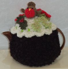a one of a kind Christmas pudding tea cosy with robin and golden berries ....knitted in with soft dark chocolate boucle yarn with a cream crochet and scalloped top.....soft and thick to keep tea nice and hot....  this cosy fits a standard, round 2 cup tea pot and measures just over 13 inches by over 6 inches....to the top of the little robin....the top of the cosy has green crackle glass beads sewn all around....  the robin in crocheted in red and brown wool with a yellow yarn beak and…