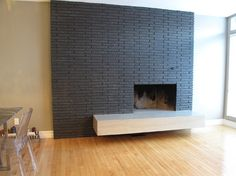 Cool Fireplace renovation. New tile on wall and concrete slab insert. Wonder how much it costs...