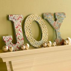 Spell a holiday greeting with letters made from wood or cut from foam core (supplies available at crafts stores). Apply holiday-theme wrapping paper to the fronts with spray glue or just paint the letters different colors. Accent the mantel display with glass ornaments or greens.