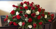 A very traditional casket spray for a closed casket. There are so many beautiful red roses in this funeral arrangement.