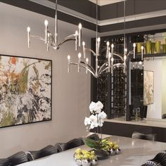 The silver architectural Draper chandelier adds a focal point in this sleek modern home dining room design project part of the 2019 New American Home. While polished detailing and tubular forms contribute to an authentic style, the candelabra socket accommodates a variety of decorative bulbs. #homedecor #home #interiordesign #diningroom #diningroomdesign #homeproject #designproject #sleek #modern #newhome #americanhome #architectural #silver #architecturallight #lighting #light #design…