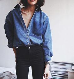 A denim shirt tucked into black pants