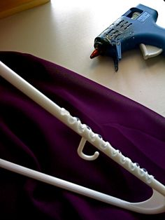 Clothes keep slipping off plastic hangers? Use a hot glue gun to apply a zig zag pattern on the arms of your plastic hangers to prevent all your wide-necked shirts from falling off. Works like a charm!