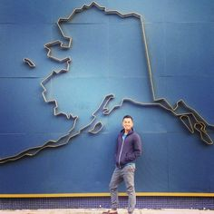 I am posing in front of a giant map of Alaska in the city of Anchorage.