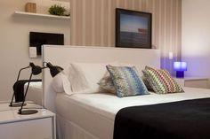 O quarto une elementos clássicos e modernos. Os lados da cama são assimétricos, com luminárias e revestimentos diferentes. De um lado da cabeceira, um espelho para dar mais amplitude ao ambiente. De outro, o papel de parede confirma a sobriedade.