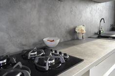 Dekorativní cementová stěrka MicroBond použitá nejen za stěnou na kuchyňské lince, ale i na samotné pracovní desce. Díky přirozenému napojení vypadá kuchyňský prostor elegantněji a čistěji. Není potřeba napojovacích lišt, které bývají rušivým prvkem. Cementová stěrka je ošetřena Gi. Gi. Sealerem, který stěrku zaimpregnuje a přidá ji na odolnosti vůči oděru, poškrábání a porušení vlivem vysokých teplot. Takto ošetřený povrch je nenasákavý a plně omyvatelný.