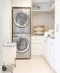 This laundry room with stacked washer and dryer features so many amazing ideas. This layout is clearly very practical and smart! Laundry bin is from Rejuvenation.