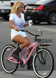 Pamela Anderson rides a pink Paul Frank Nirve cruiser bicycle
